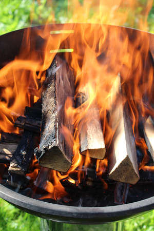 Charred wood and bright flames on dark background Stock Photo