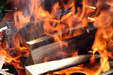 defiance: Charred wood and bright flames on dark background Stock Photo