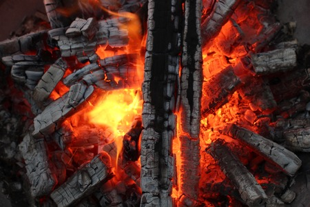 fervour: Charred wood and bright flames on dark background Stock Photo