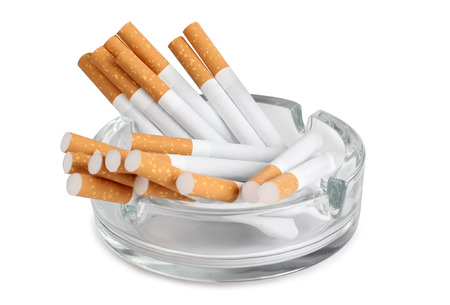 Glass ashtray and cigarette on white background