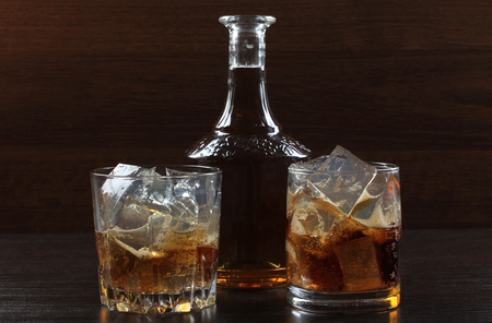 Glass and bottle whiskey on wooden table Stock Photo