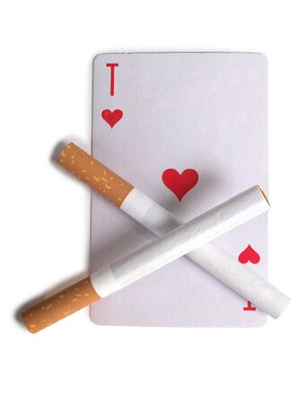 Cigarette with a filter and playing cards on a white background Stock Photo