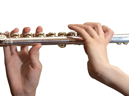 Metallic flute in female hands over white background