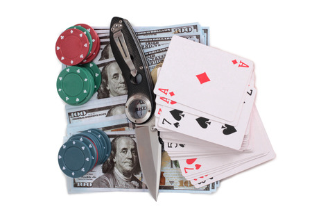 Playing cards and folding knife on a white background Stock Photo