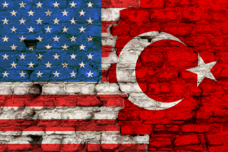 Flags of america and turkey is painted on a brick background