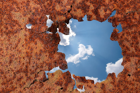 Blue sky and clouds in a metal wall break
