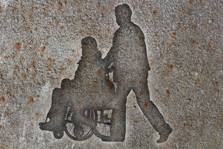 Silhouettes wheelchair and man on a brick wall Imagens