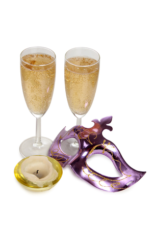 Glasses with champagne and carnival mask on a white background