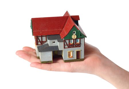 Plastic model of an old house in female hands on a white background Фото со стока