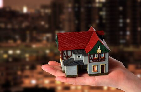 Toy house in hand on a background of a modern city