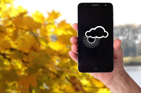 Smartphone in a female hand on a background of natural landscapes. Weather forecast image Stock fotó