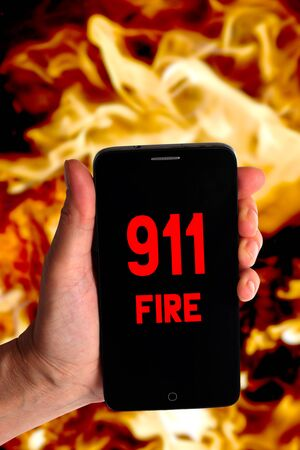 Smartphone in a female hand with a signal for help on a background of fire