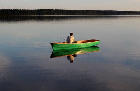 Fisherman in a wooden boat on a large lake Imagens