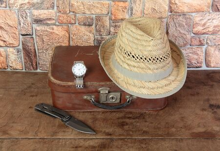 Old suitcase and personal items on a wooden table