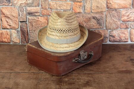 Old suitcase and hat on a wooden table