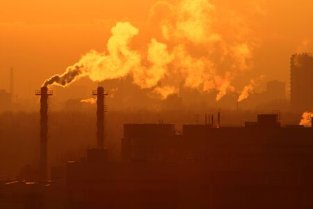 Smoke from a factory chimney against evening sky. Image on theme of global warming