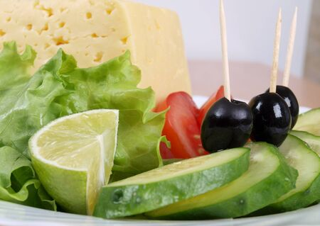 Salad of black olives, tomatoes and cucumbers on a porcelain plate Banque d'images