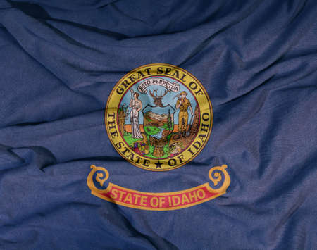 Flag of the American state flies in the wind. Colored background on fabric 写真素材 - 154854448