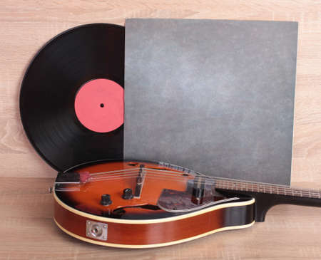 Vintage vinyl discs and country mandolin on wooden background