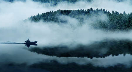 Quiet mountain lake in a thick fog  In the background a mountain forest  Floats on the water in the boat people  The blue tone