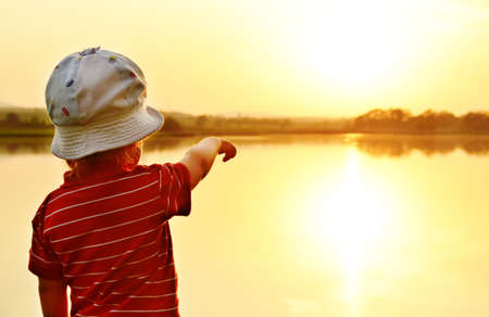A little boy stands on the shore of the lake and watching the sunset  Orange background