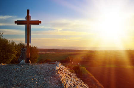 lone Christian cross on stony Hill, against the backdrop of fields and mountains  Bright Sunny rays
