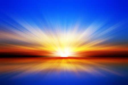 Sunset over the sea  Blue sky  Red horizon  Yellow sun rays Standard-Bild