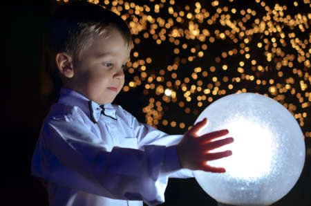 boy in a white shirt holds in hands glowing ball.