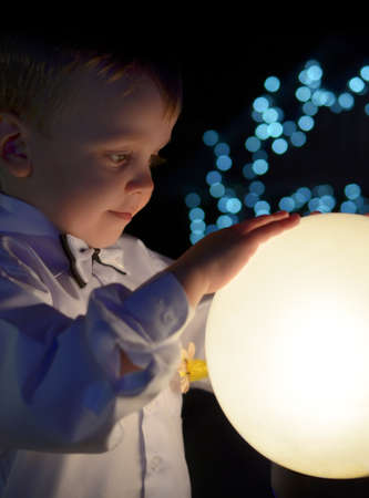 boy in a white shirt holds in hands glowing ball. Stock Photo - 25089084