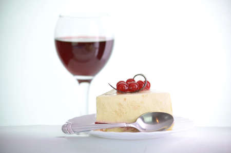 glass of wine next to slices of cake with the white a plate of on the white background