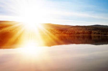 Bright orange sun rays over mountain lake