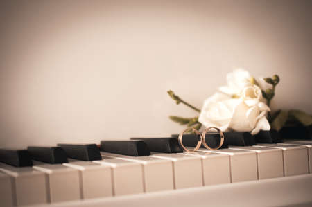 old photograph: Two wedding rings are on the piano, near the roses. Imitation of an old photograph. Stock Photo