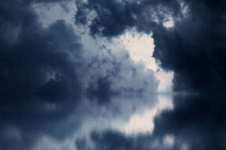Dramatic dark clouds rise above the sea. Blue watercolor. photo