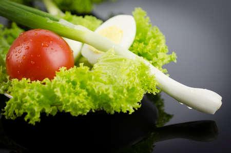 Fresh lettuce, boiled egg tomato, onions on a black table