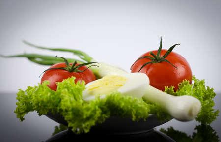 boiled egg: Fresh lettuce, boiled egg tomato, onions on a black table