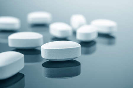 reflective: Closeup of medicine tablets on reflective surface