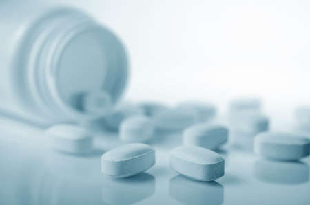 Closeup of medicine tablets spilled from bottle