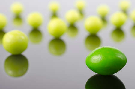 dragee: Sweet green dragees on the reflective surface