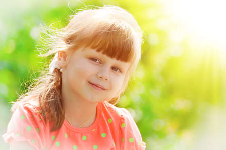 sweetly: Little girl in a pink dress, lit by the rays of the sun - smiles sweetly.