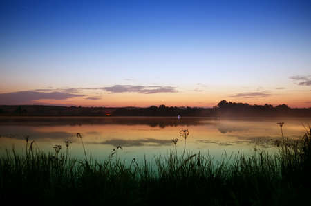 early summer: Vivid pre-sunrise colors  lake on a summer morning Stock Photo