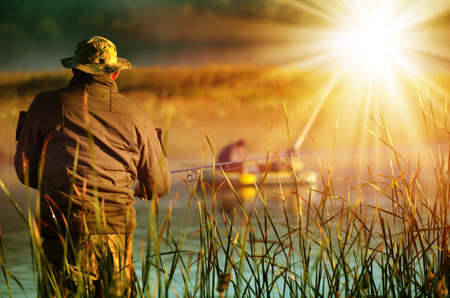 fishing lake: Fisherman, illuminated by the sun, standing in the reeds and catches fish