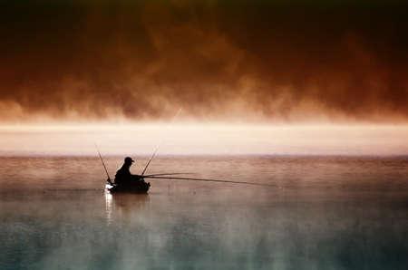 Mañana en el lago. Un pescador se sienta en el barco y las capturas de peces Foto de archivo - 47843138