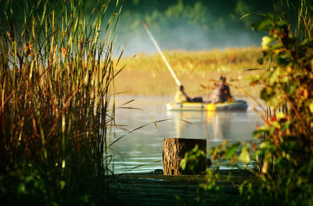 fished: Lumen of between the reeds on the lake. Two fishermen fished with a boat. Stock Photo
