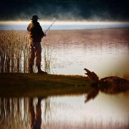 fisherman: Morning on the lake. A fisherman stands on the shore and catches fish. Reflection in water