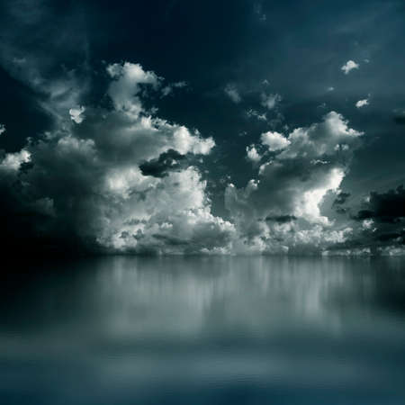 rise above: Dramatic dark clouds rise above the sea. Blue watercolor. Stock Photo