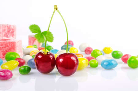 dragees: Two red cherry, and multicolored dragees lie on a white surface