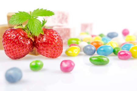 dragees: Two red strawberries, and multicolored dragees lie on a white surface Stock Photo