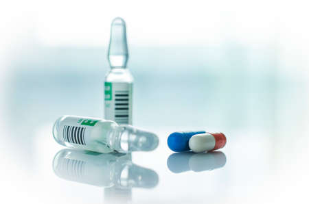 medical care: Glass vials of clear liquid and pills are on the light surface.