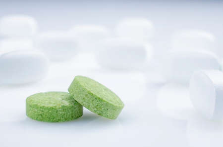 white pills: Close-up. Two green pills on a light background, and white pills