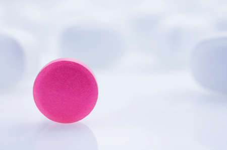 white pills: Close-up. Pink pill on a light background, and white pills